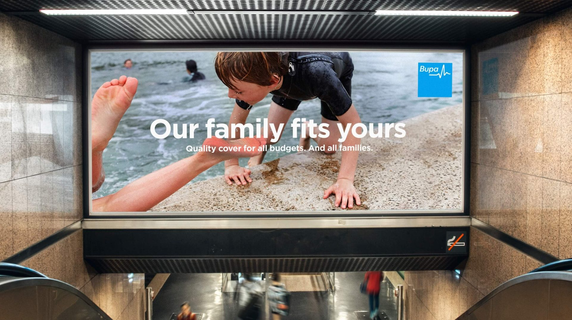 A billboard above a pair of escalators advertising Bupa family cover, with a photo of a young boy climbing out of a pool
