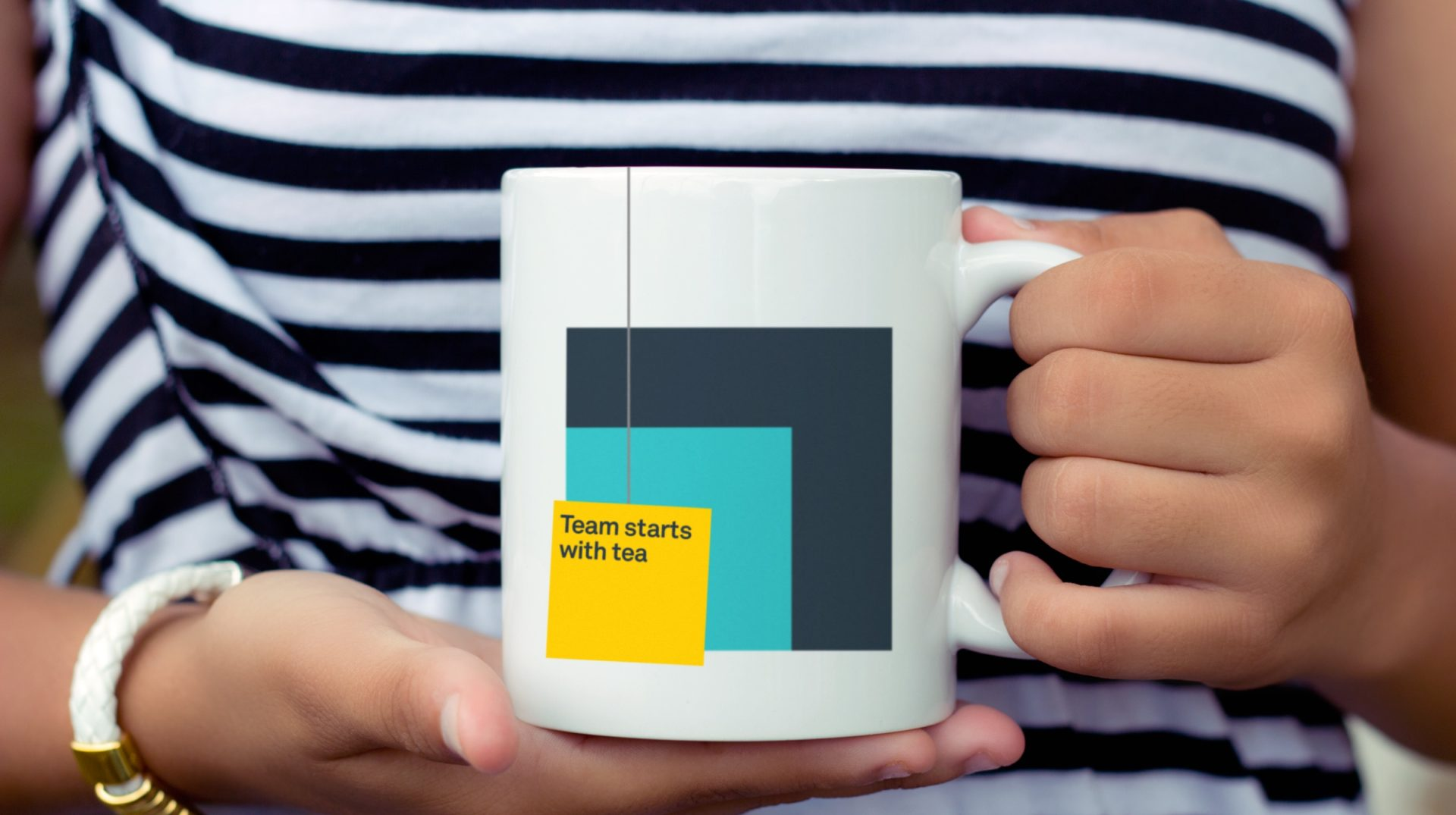 "A branded mug with ""Team starts with tea"" printed on the side"