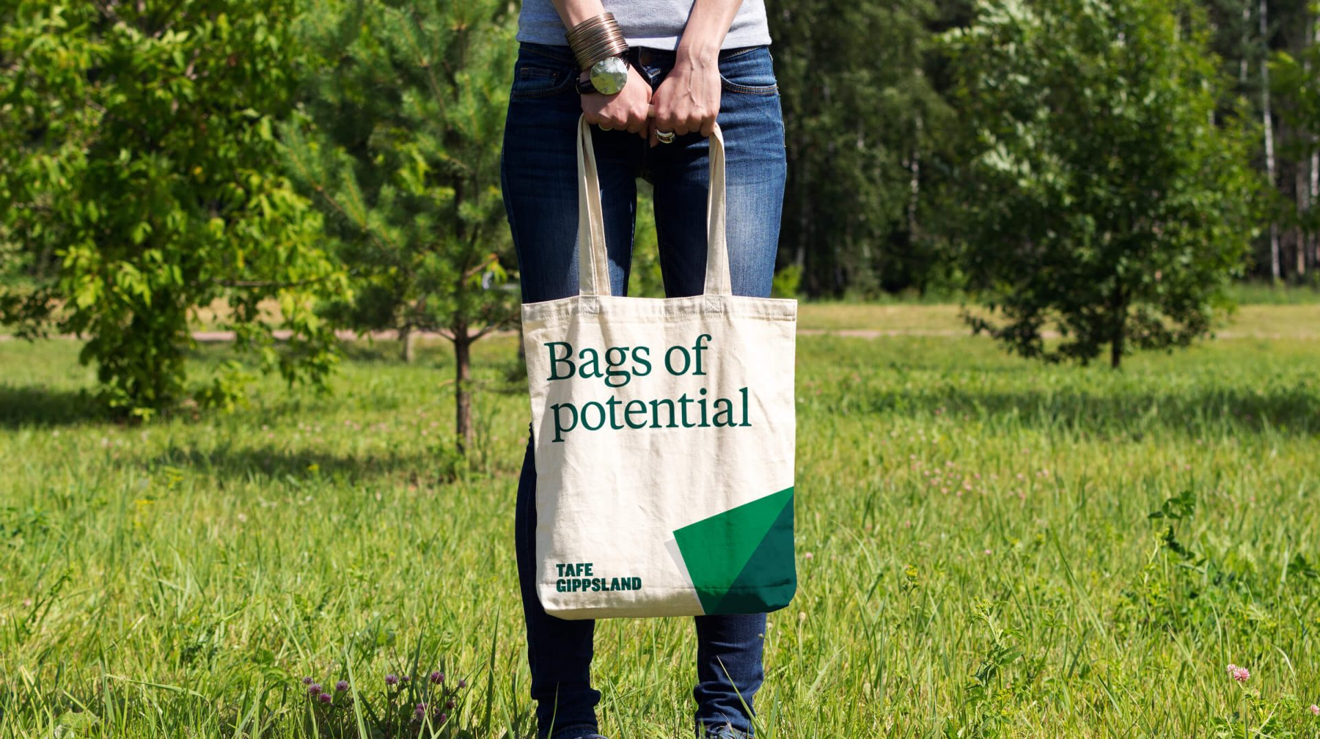 A woman standing in a grassy area holding a canvas bag that says 'Bags of potential'