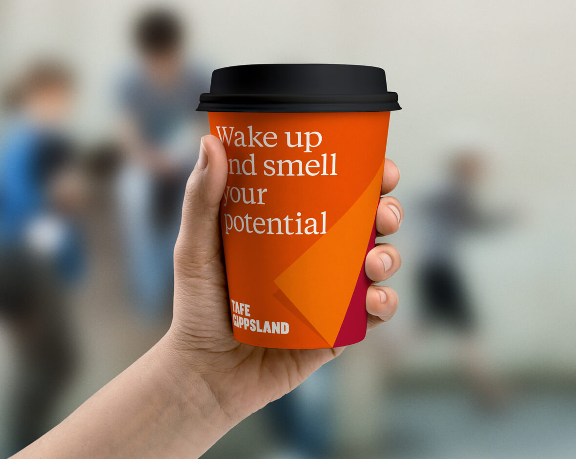 A orange takeaway cup with 'wake up and smell your potential'