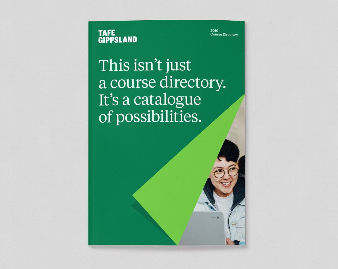 Green cover of the 2019 Course Directory, with the image of a male student using a computer revealed by a folded corner