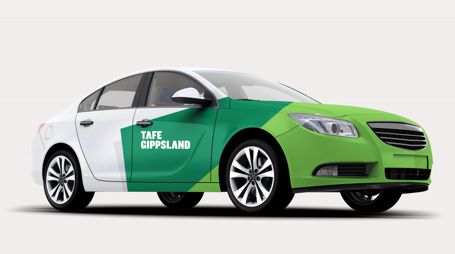 A sedan with the front wrapped in dark and light green, and the TAFE logo on the side