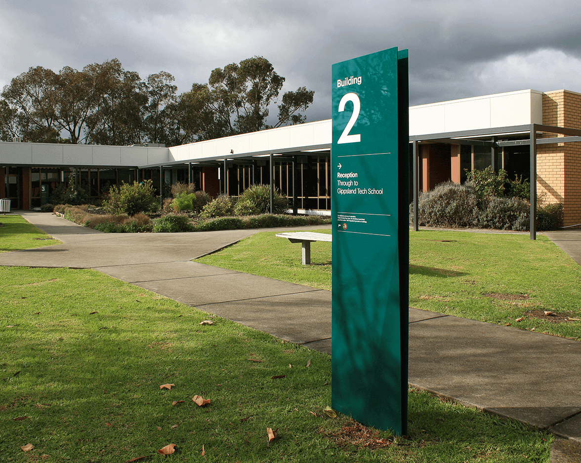 Dark green signage for Building 2 outside a building at a TAFE Gippsland campus
